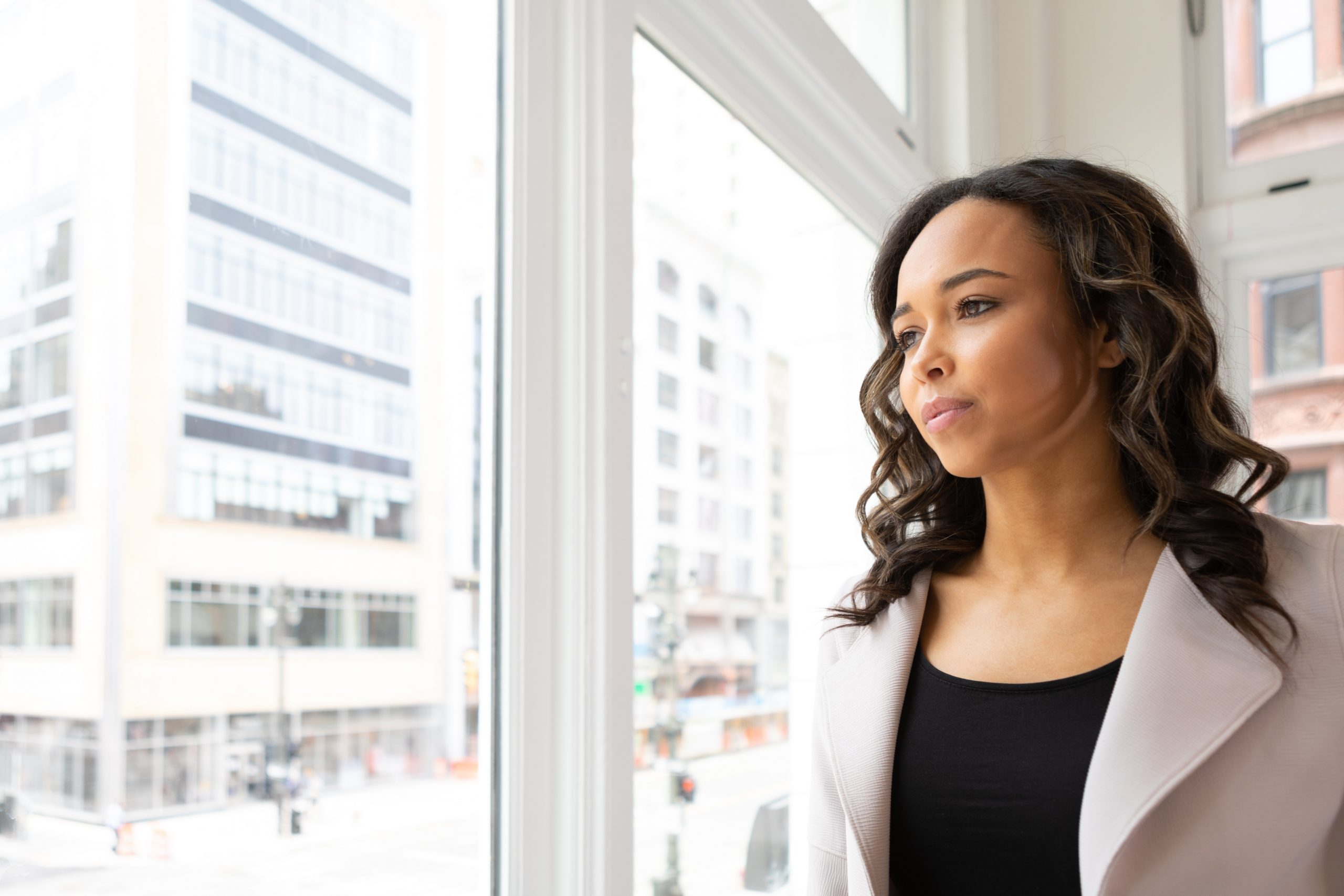 black woman in blazer looking out window